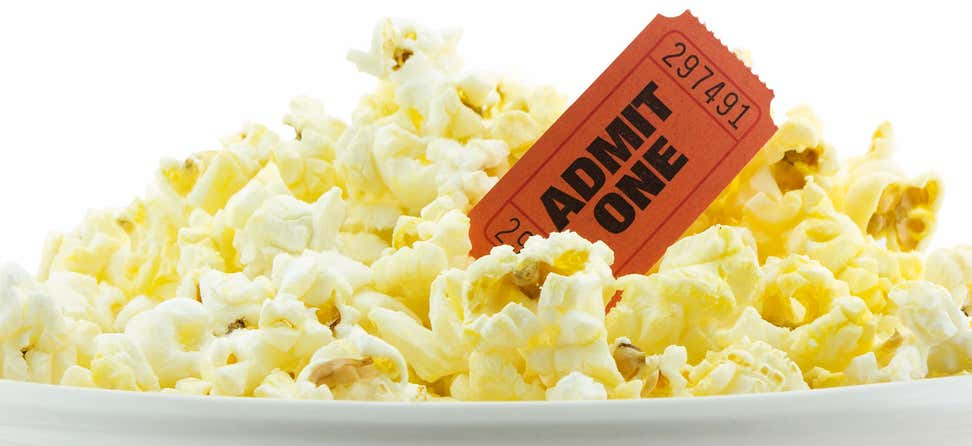 "An up close shot of a bucket of popcorn and a ticket that says ""Admit One""."