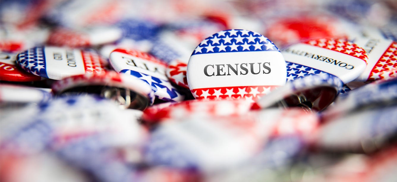 """A pile of red, white, and blue political buttons with one facing the camera that reads """"CENSUS"""" ."""