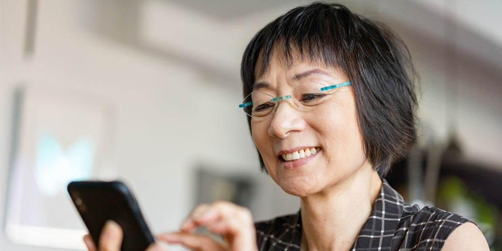 A senior Asian woman is using her smartphone, smiling.
