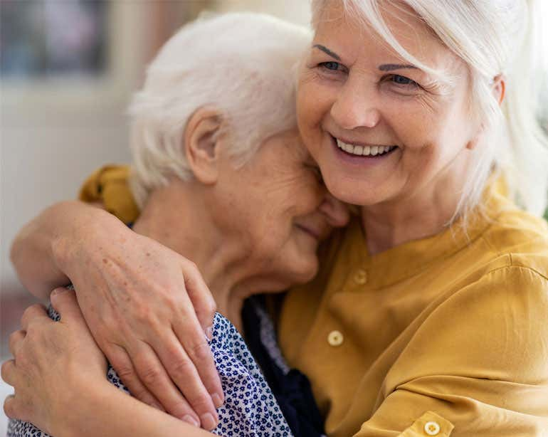 A Caucasian senior woman embraces her mother while smiling.