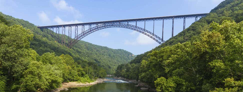 A beautiful, scenic picture of a massive steel bridge surrounded by mountains and a stream running underneath.