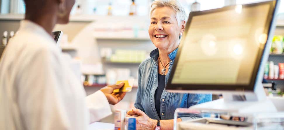 A black female pharmacist is returning the credit card to female senior woman after receiving the payment.