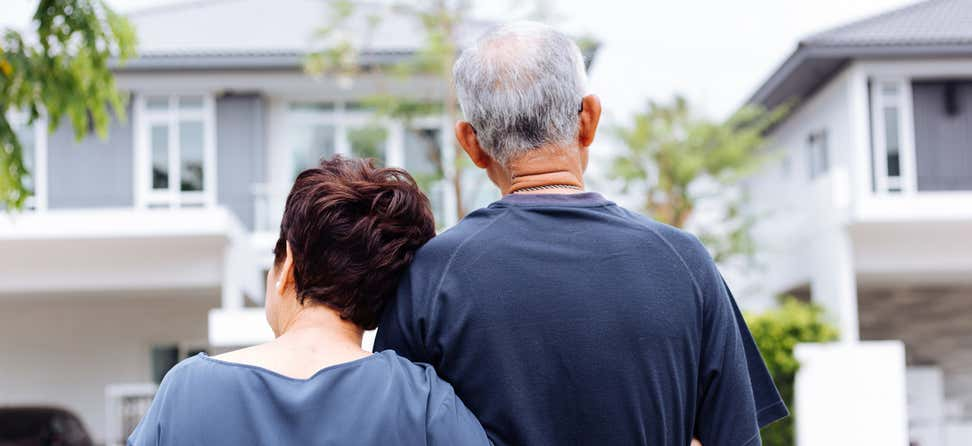 A back shot of a happy senior couple looking on from their house to the street.