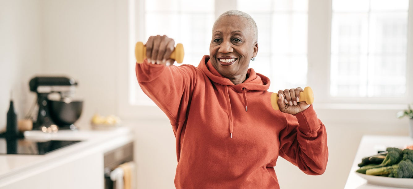 A senior black woman is doing strength exercise with dumbbells in her home.