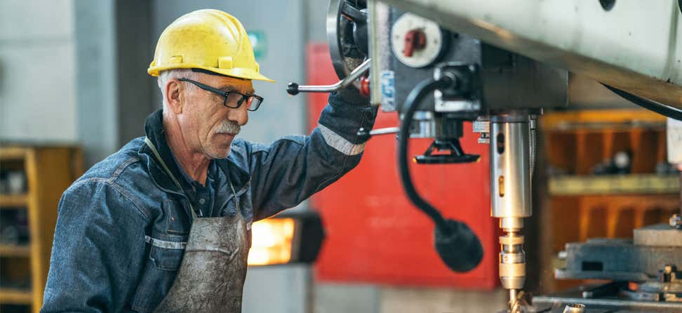 A senior man with a yellow hard hat and glasses works with a large drill bit at a plant workshop.