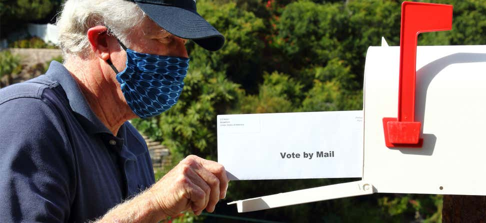An older masked man is placing his ballot for the 2020 election in the mailbox.