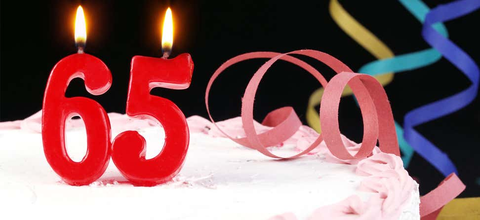 Birthday cake with candles reading 65