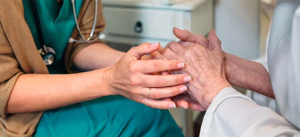 A nurse holds the hands of a female senior.