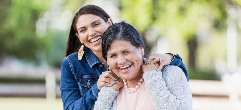 Hispanic daughter puts hands on shoulder of her older mother, both smiling