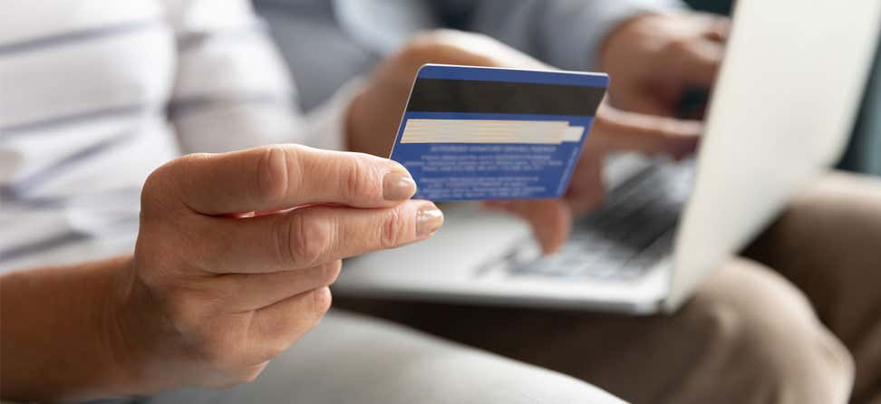 A closeup shot of a wife holding her credit card while her senior husband has the laptop ready for payment.