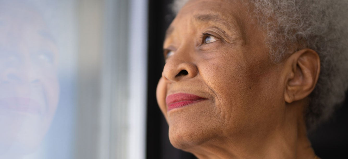 A lonely Black senior woman is looking out of her window.