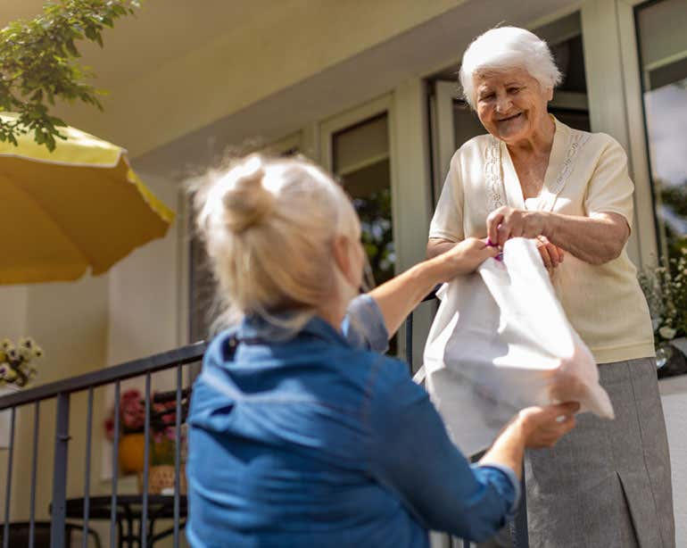 A middle-aged female Caucasian caregiver is handing groceries to her older mother while she's on the porch.