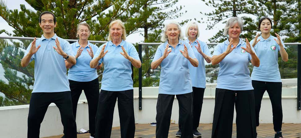 Dr. Paul Lam and other older adults participate in a sun style tai chi workshop together outside.