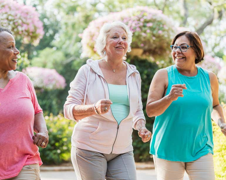 Three senior women are exercising together outside.