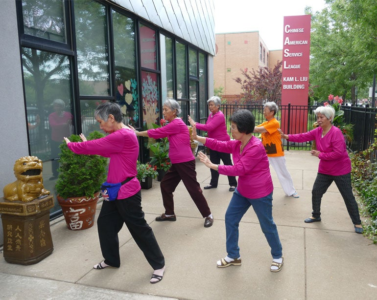Chinese American women in pink shirts practicing tai chi outside
