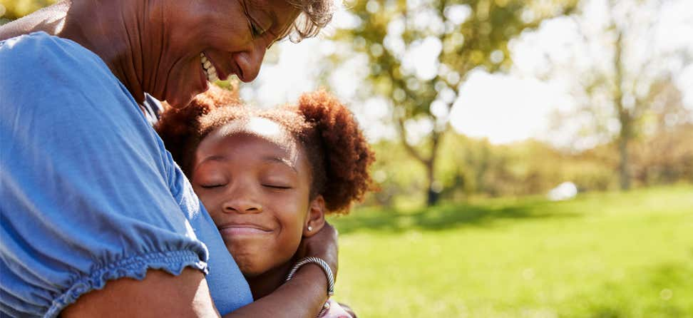 A close up of a Black senior woman hugging her granddaughter in the park.