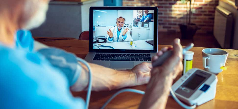 A senior man has a telehealth appointment with his doctor during the pandemic.