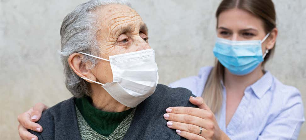 A younger female caregiver puts her hands on the shoulders of an elderly woman wearing a mask because of COVID-19 pandemic.
