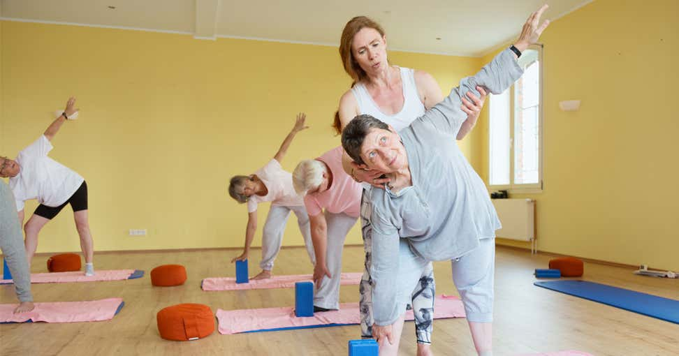 A senior Caucasian woman is getting help from her instructor during her yoga class at a local senior center.