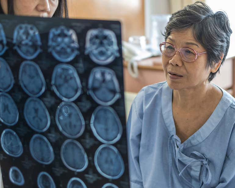 A senior Asian woman looks at Magnetic Resonance Imaging (MRI) film for neurological medical treatment with her doctor.