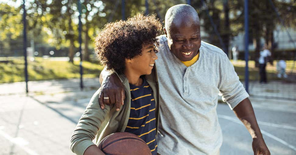 A senior Black man is outside playing basketball with his grandson.