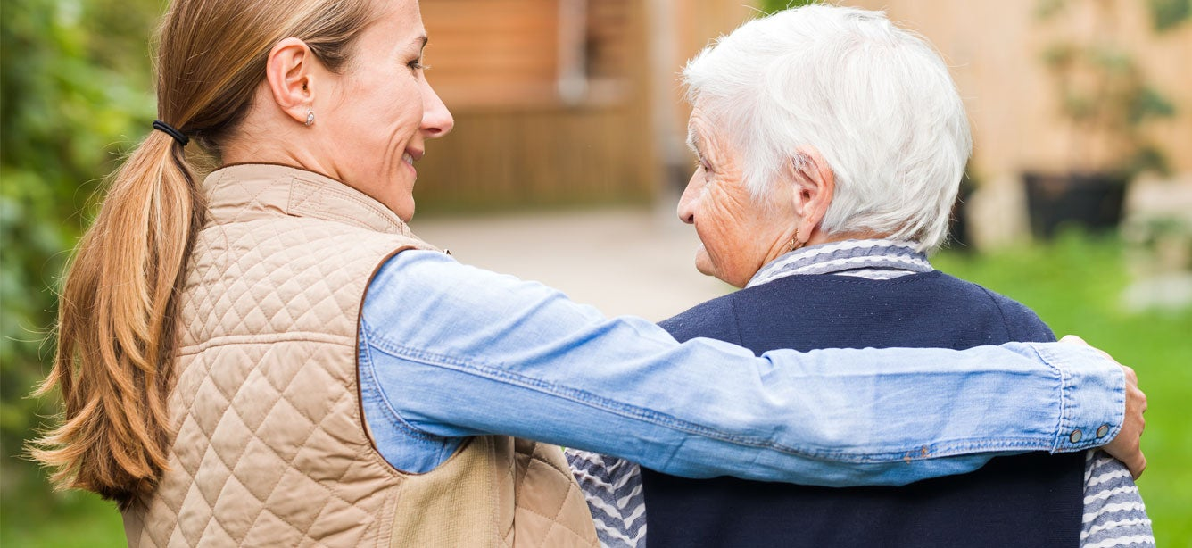 A young senior center professional is walking a client in the courtyard.
