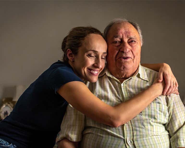 A Hispanic young, female caregiver hugs her senior father while sitting at home.