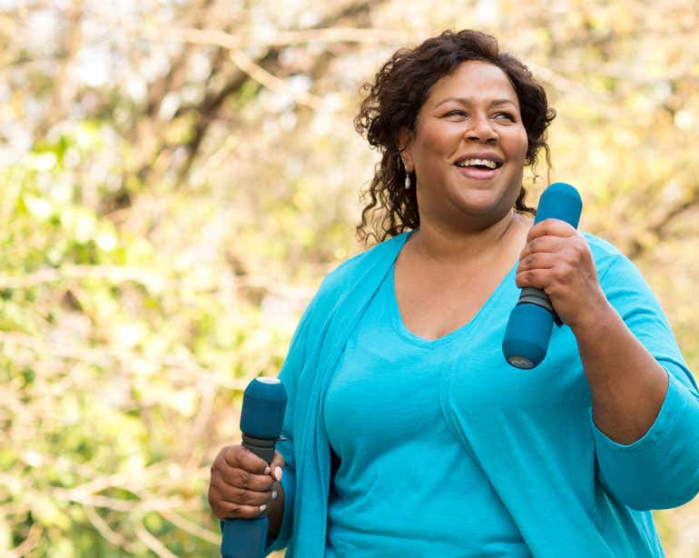 A senior Black woman wearing teal activewear is outside in the park walking while carrying hand weights.