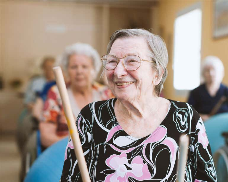 A senior caucasian woman is in a senior center, playing with a drumstick during a group activity.