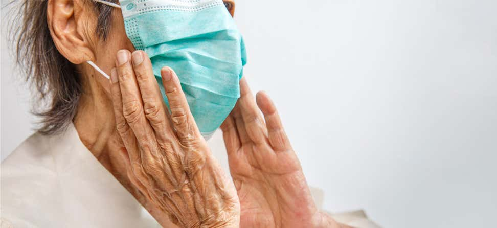Close up shot of a senior woman wearing a mask, where her hands are close to her face.