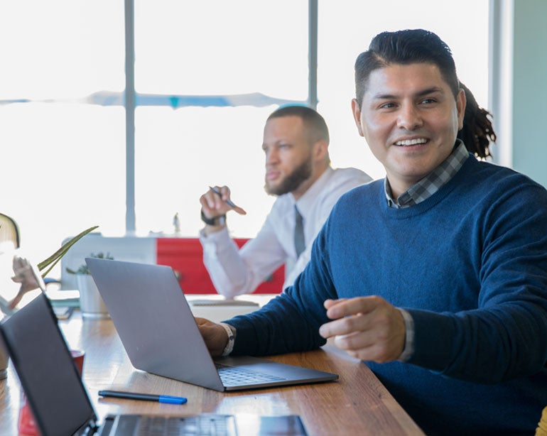 A Hispanic mail professional is setting in a meeting looking at his laptop and explaining material to another colleague.