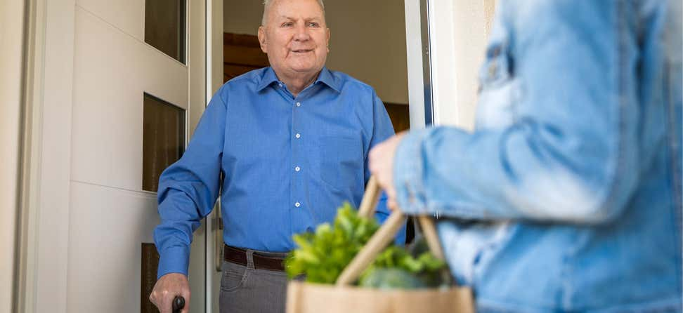 Older Caucasian man is receiving food delivery at home.