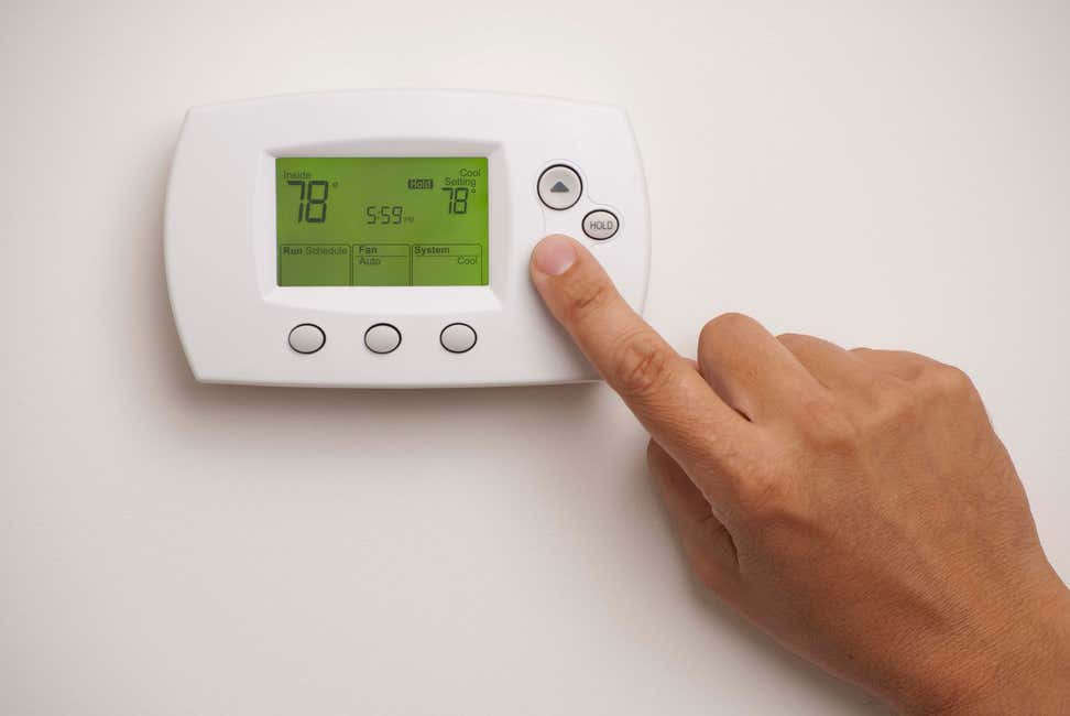 Hand pointing to digital thermostat on wall
