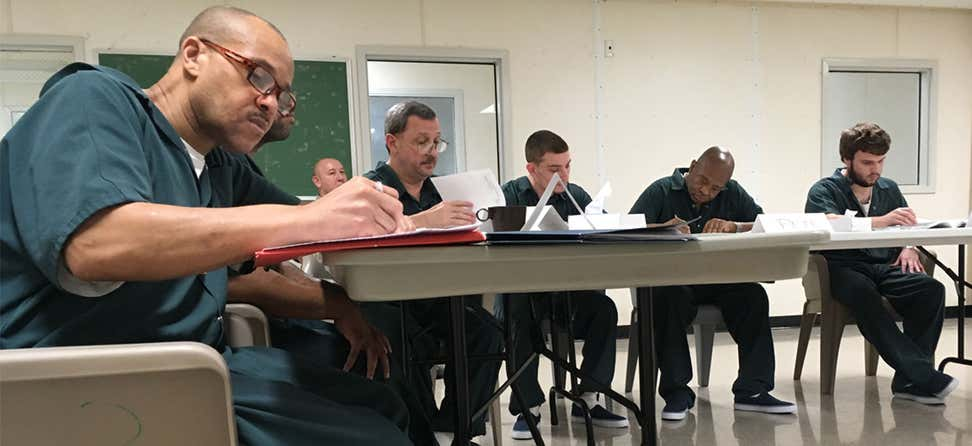 A group of prisoners of all ages are in a classroom setting filling out paperwork, studying together.