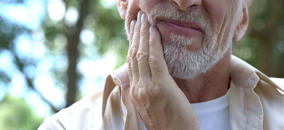 An older man is seen placing his hand near his face, indicating a tooth ache.