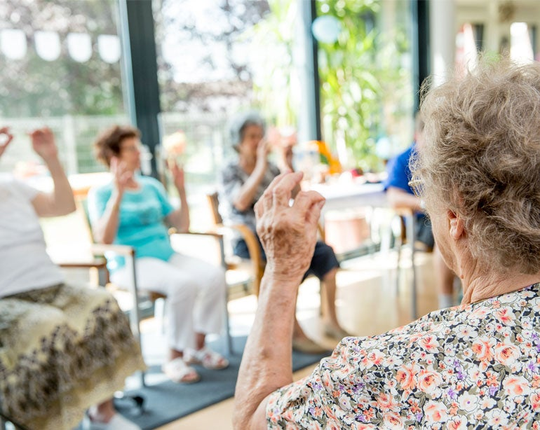 A senior woman and other older adults are playing a group activity, exercising together in a senior center.