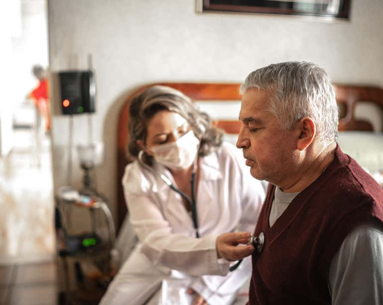 A nurse is listening to the heartbeat of a Hispanic senior man.