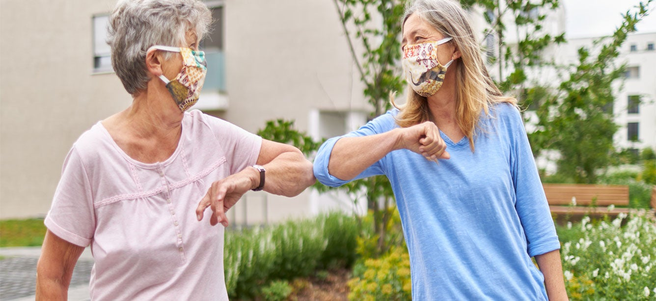 Two older women, standing outside and visiting during the pandemic, are elbow bumping while wearing masks.