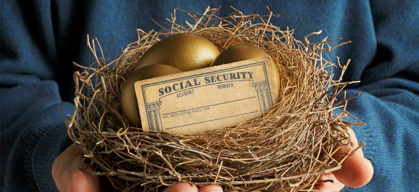 An older man holds a nest that contains two golden eggs and a blank social security card.