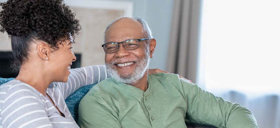 A senior Black man is smiling while looking at his middle-aged female caregiver.