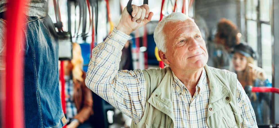 A senior man, wearing plaid and other outerwear, is standing up on a bus and enjoying his day.