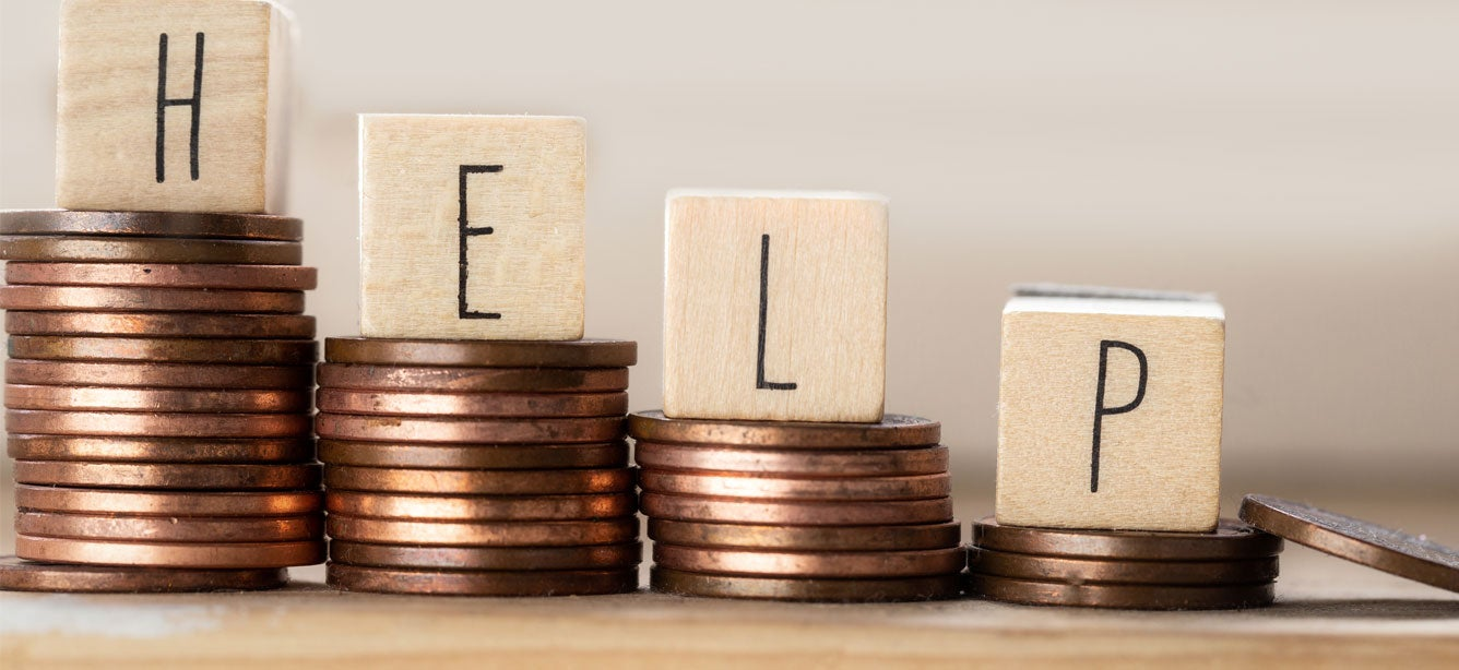 """A line of wooden cubes with the word """"Help"""" and pile of coins are staircased to signify how to boost your budget."""