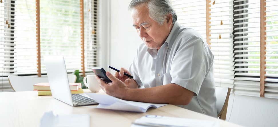 An older Asian man sits at his kitchen table, working on his finances in front of a computer and holding a calculator.