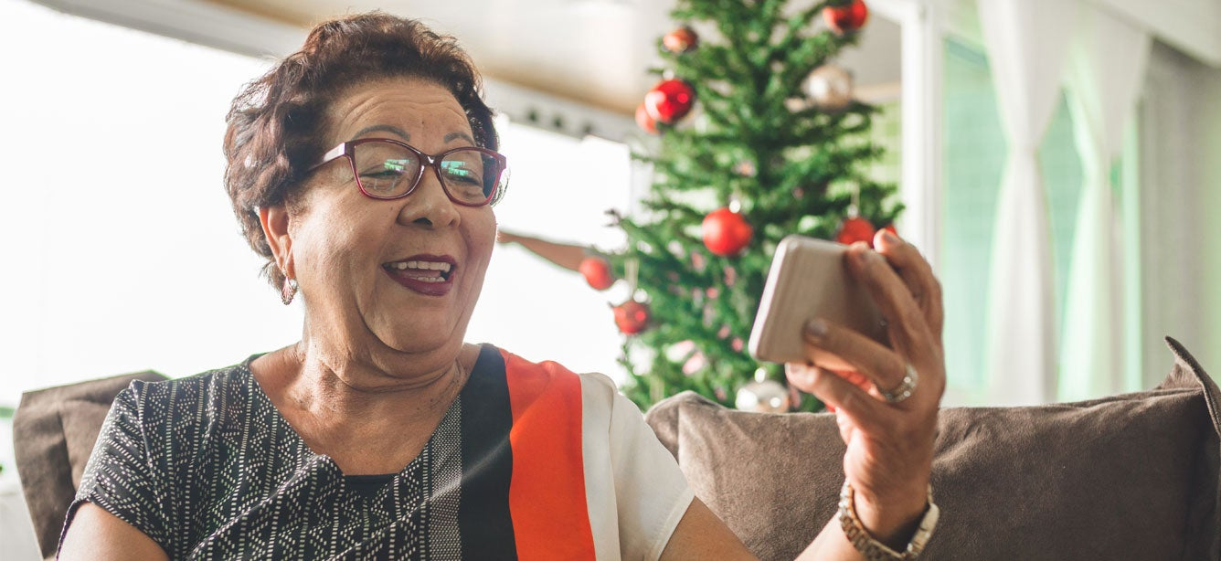 A senior Asian woman is holding her phone video chatting with a loved one during the holiday.
