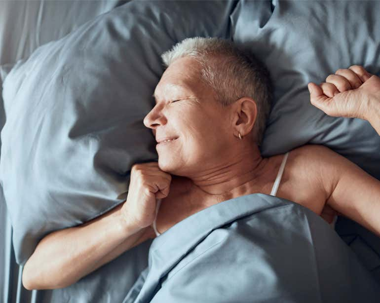 A senior woman is waking up after a restful night's sleep, smiling as the sun shines in her room.