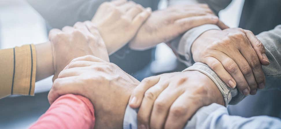 A group of aging services professionals are holding hands in a circle, indicating strength in numbers.
