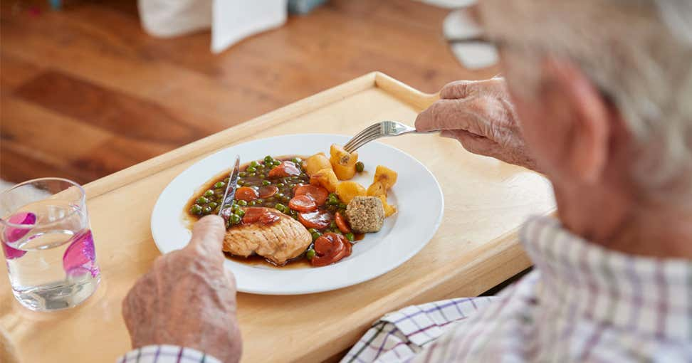 A senior Caucasian man is eating a well-balanced dinner at his table.