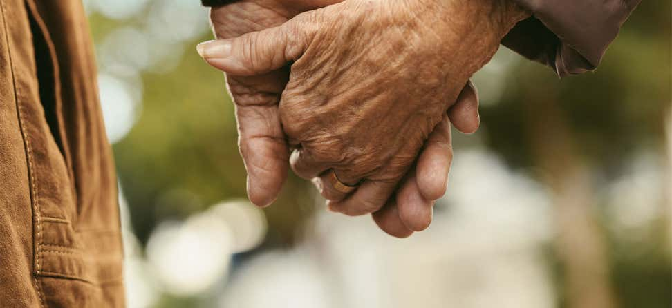 A closeup of a senior couple holding hands while walking outdoors.
