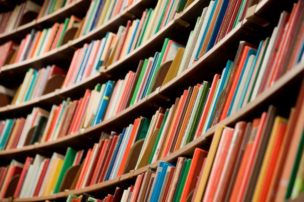A photo of a library's shelves with many colorful books.