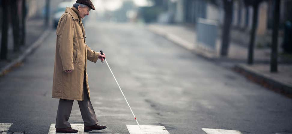 A senior man suffering from vision loss, wearing a khaki trench coat is walking across the street using walking stick.
